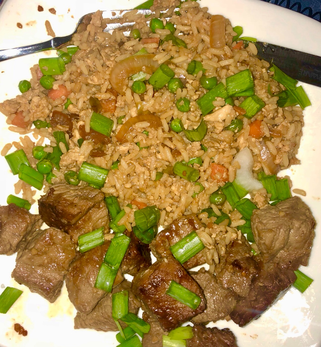 Steak bites are sitting on a white plate with fried rice.