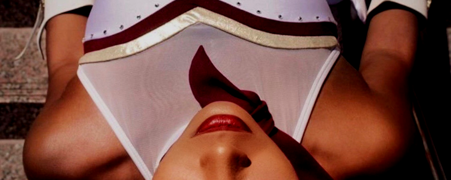 An image taken of Ravyn Ammons laying down from above. She is wearing a white Strutters uniform with a hat covering one of her eyes.