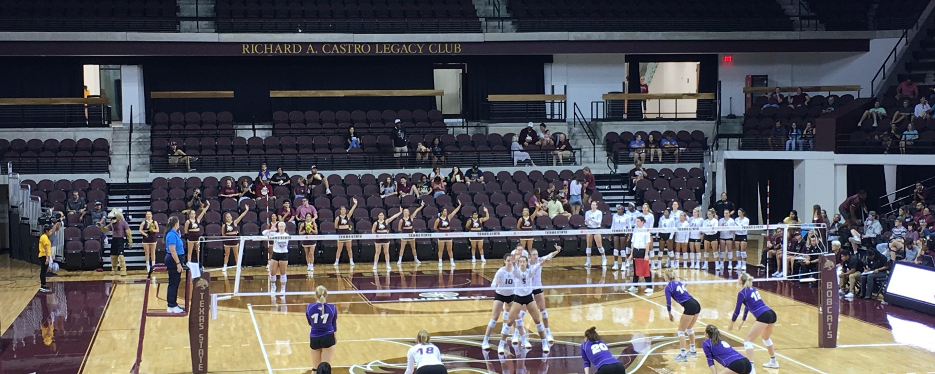 Northern Iowa prepares to recieve the ball from Texas State's server, while Texas State, standing towards the front of the net in a diamond formation, waits for the ball to be served.