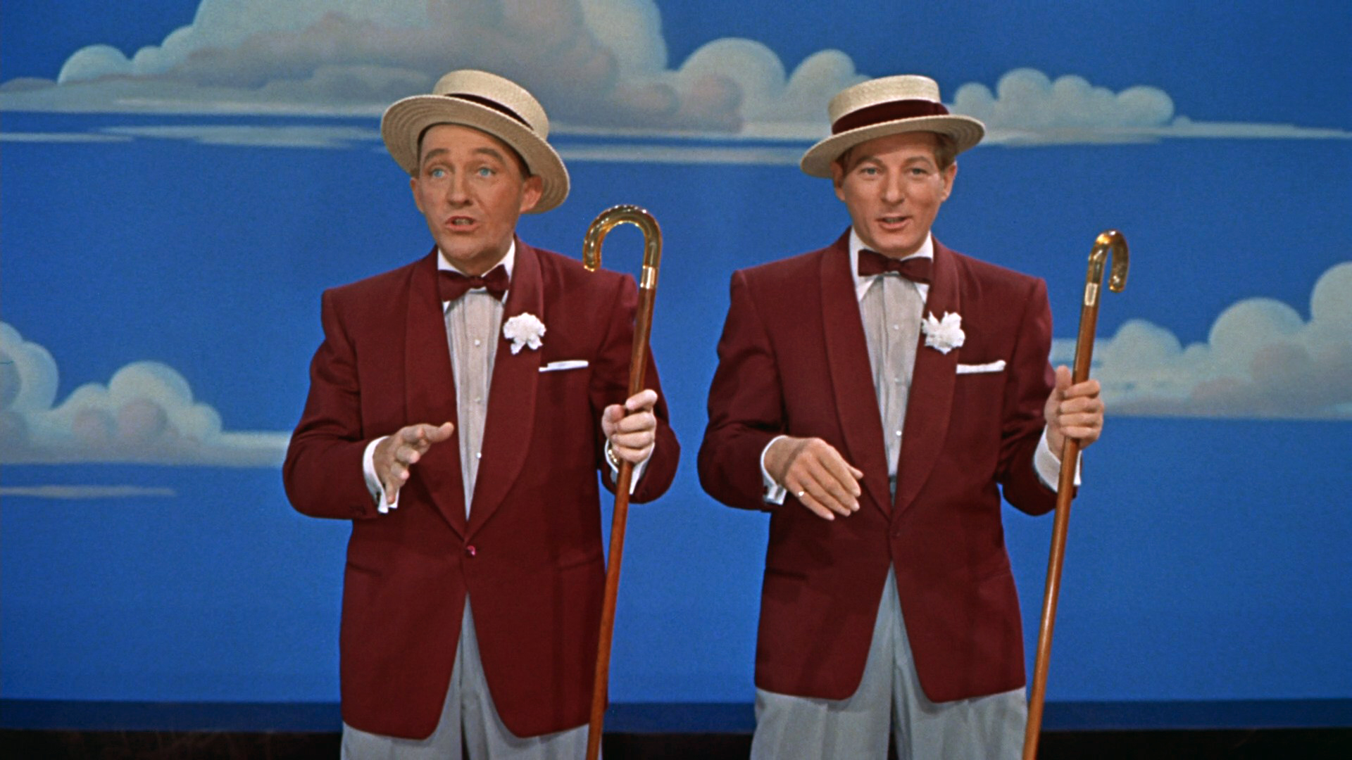 Danny Kaye and Bing Crosby standing in front of a blue background with white clouds scattered. They are wearing short, flat-brimmed straw hats, maroon suit coats, and each holding a cane in their left hand.