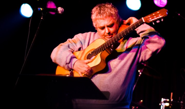 Daniel Johnston putting his guitar strap over his neck