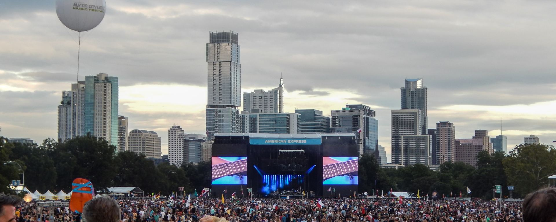 Thousands of people make their way to the biggest stage at Austin City Limits. You can see the Austin skyline behind the stage.