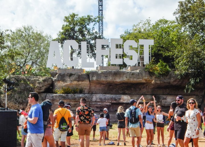 Multiple groups stand in front of a giant sign that reads ACL FEST in bold letters. Some are talking, taking photos of each other, or relaxing under the shade of the many trees surrounding the sign.