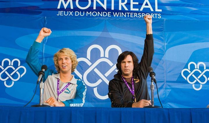"Two men on a panel at a press conference after a figure skating competition, both holding their fists in the air with the title ""Montreal Jeux De Monde Wintersports"" displayed behind them."