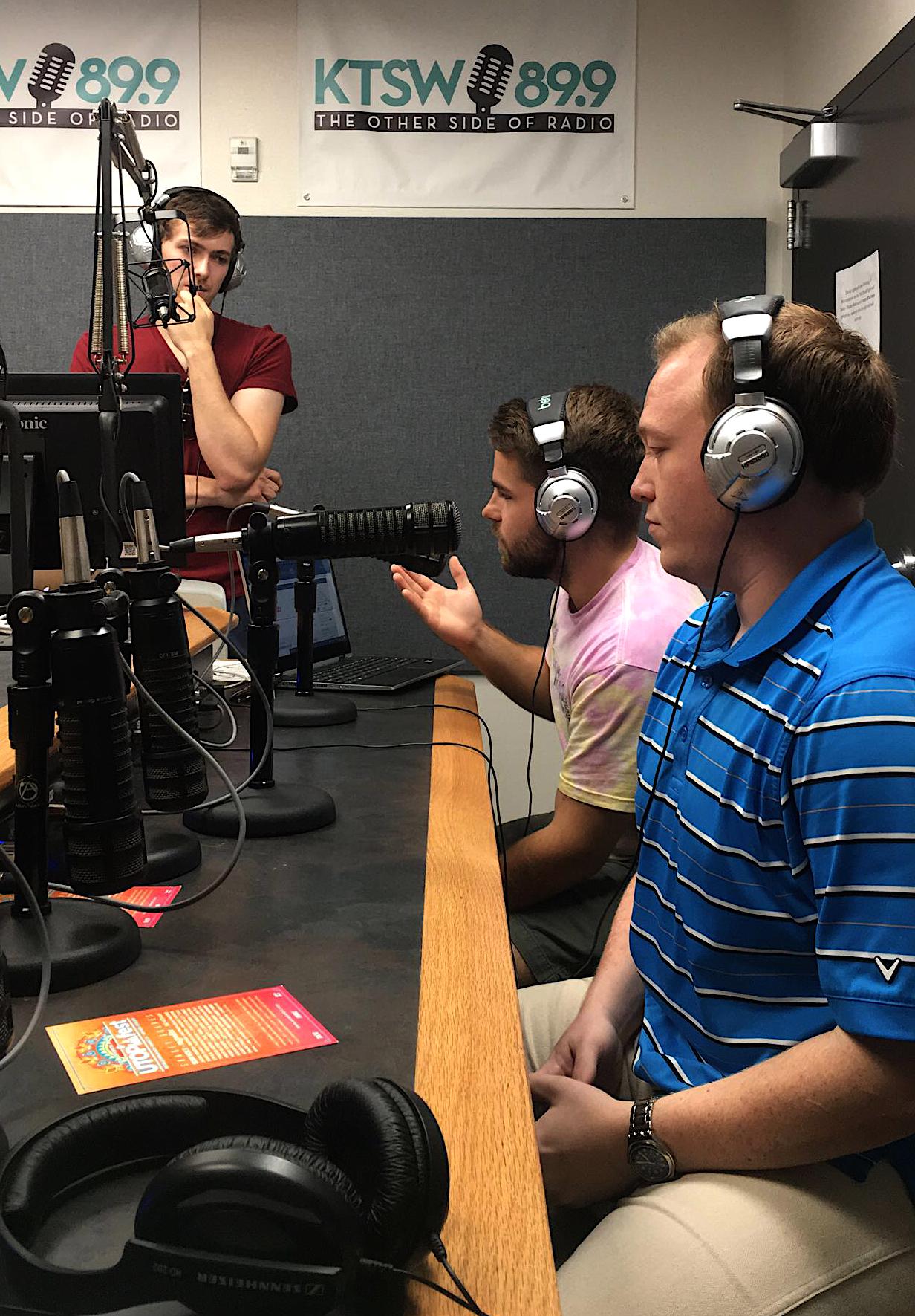3 KTSW student workers in the studio with headphones on speaking into microphones.
