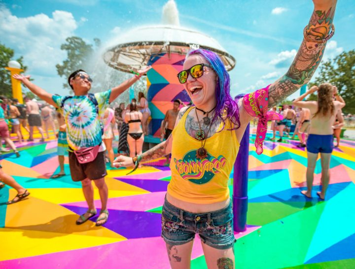 People smiling in the sunshine at the iconic fountain at Bonnaroo Music & Arts Festival.