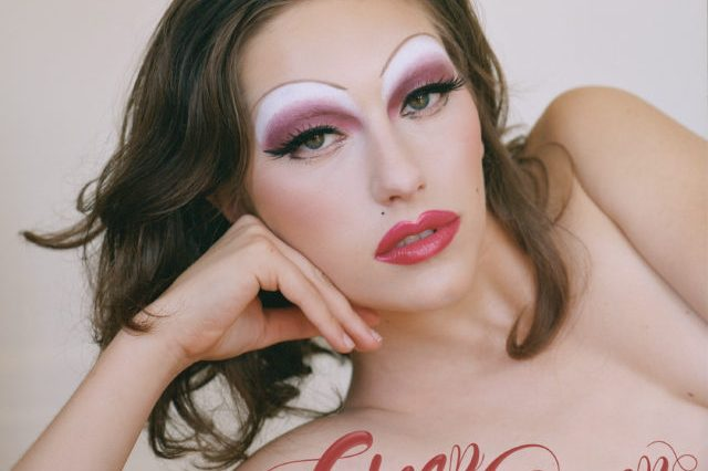 "Album cover hard showing King Princess laying down on her arm with drag makeup on, featuring pink and white eyeshadow. The words ""Cheap Queen"" are placed at the bottom in red, cursive writing."
