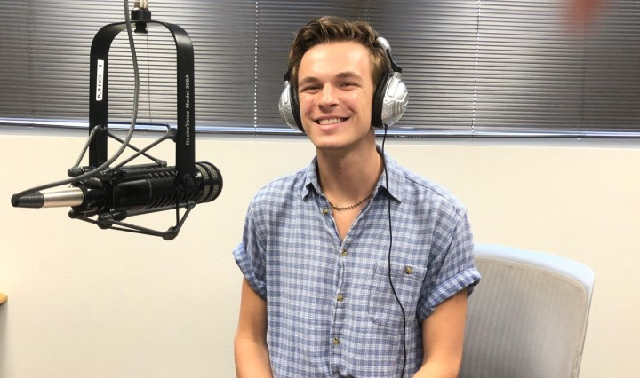 Conner Yarbrough, white male, sits in the KTSW studio booth with headphones on while wearing a checkered blue and white shirt.