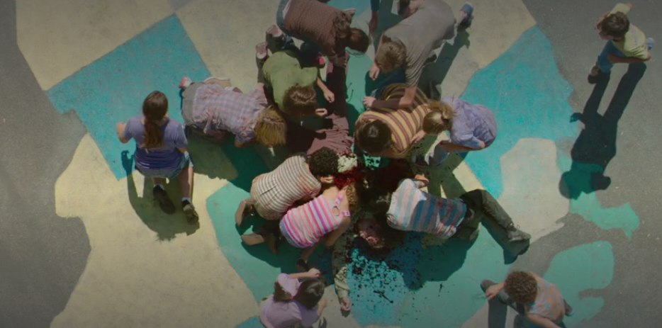 Zombie children covered in blood surround a man's body as they eat him on a cement floor of a playground