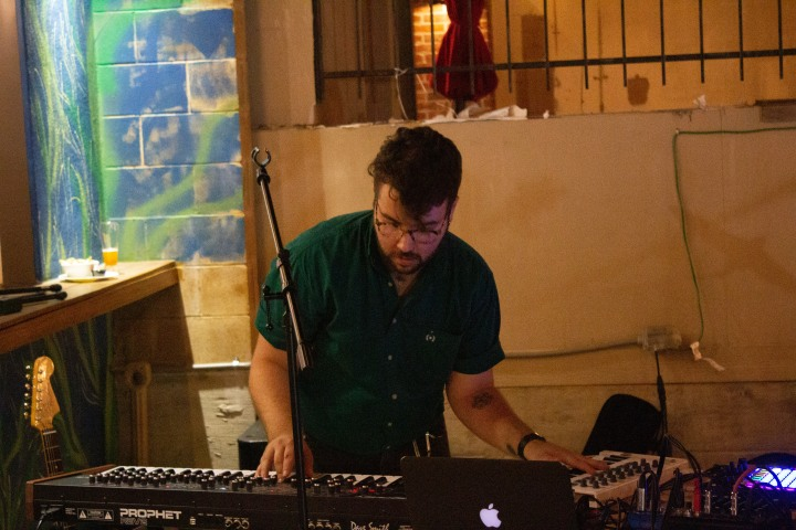 a band member reaches across two synthesizers during a live performance. The musician is wearing a green shirt and glasses and has a beard