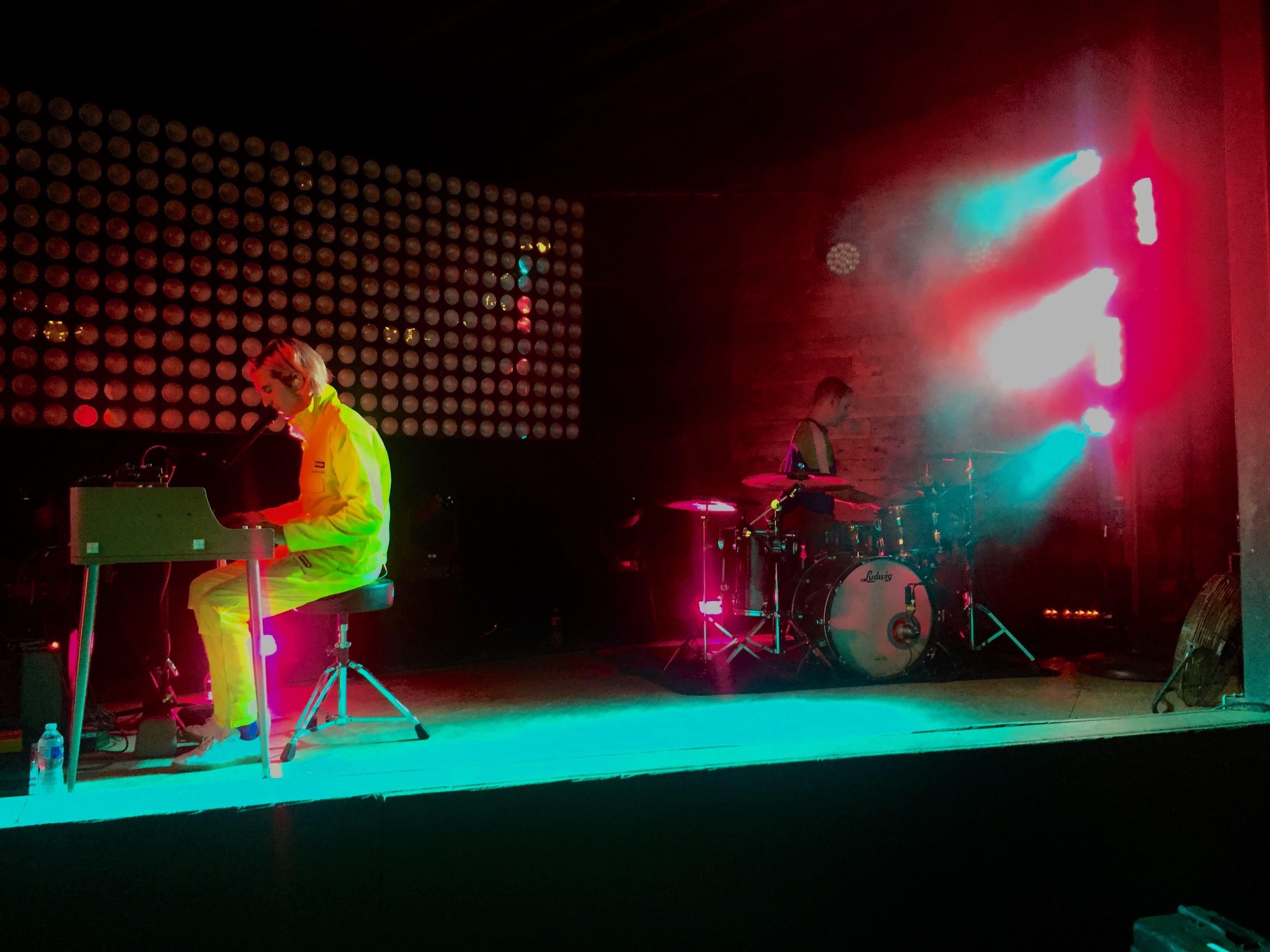 Two men performing on a stage. On the left, a man in a yellow jumpsuit plays an electric keyboard. On the far right, a man plays drums. Blue and red lights create a stark contrast.