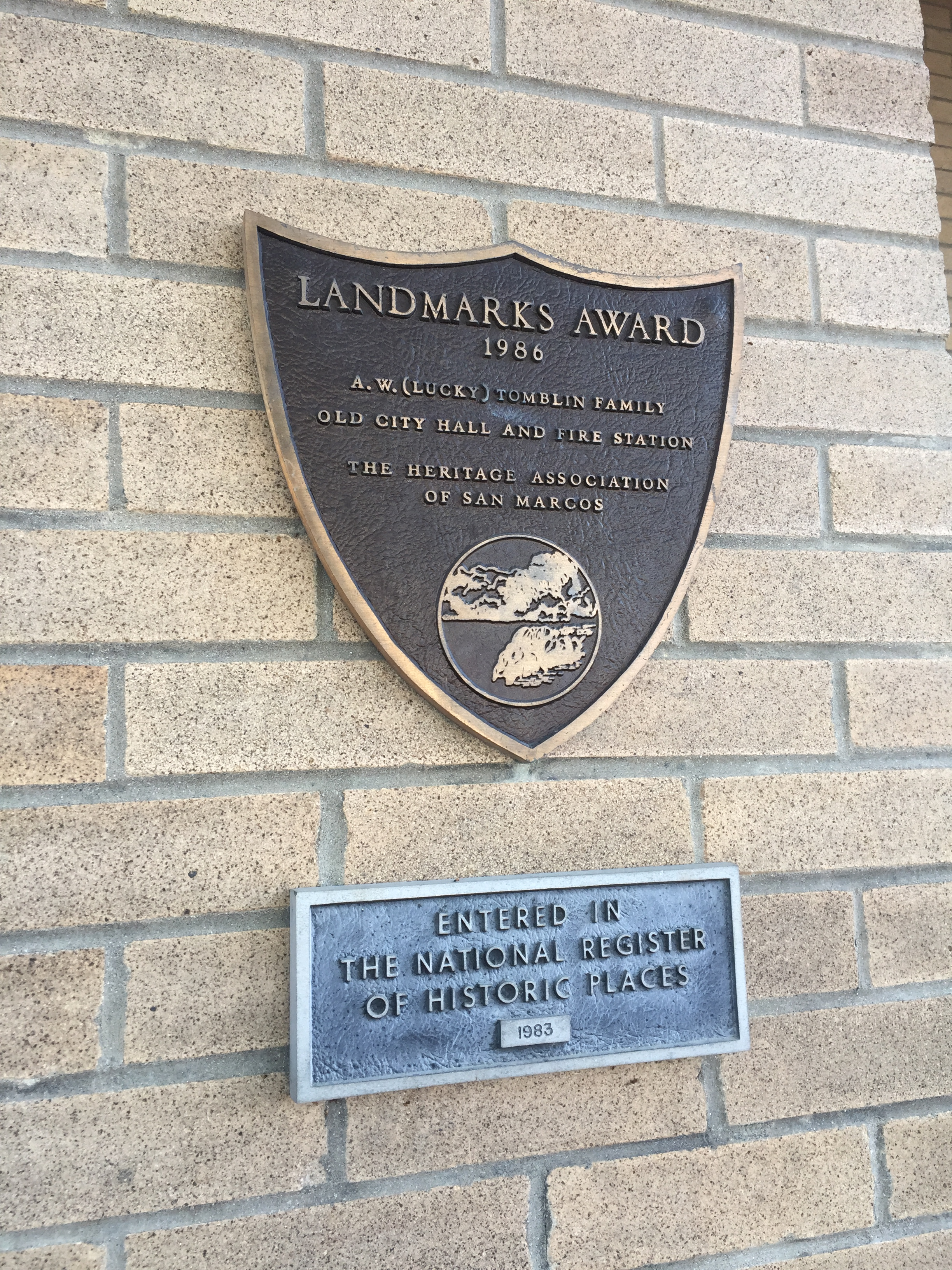 """Two plaques on a brick wall. The top plaque reads """"Landmarks Award, 1986. A.W. (Lucky) Tomblin Family. Old City Hall and Fire Station. The heritage association of San Marcos."""" The bottom plaque reads """"Entered in the National Register of Historic Places, 1983."""""""