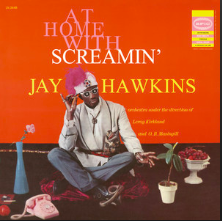"Singer Screamin' Jay Hawkins sits Indian style against an orange background. He is surrounded by vases and flowers and wears a white and purple hat and sunglasses. The words ""At Home with Screamin' Jay Hawkins"" reads in large font behind him."