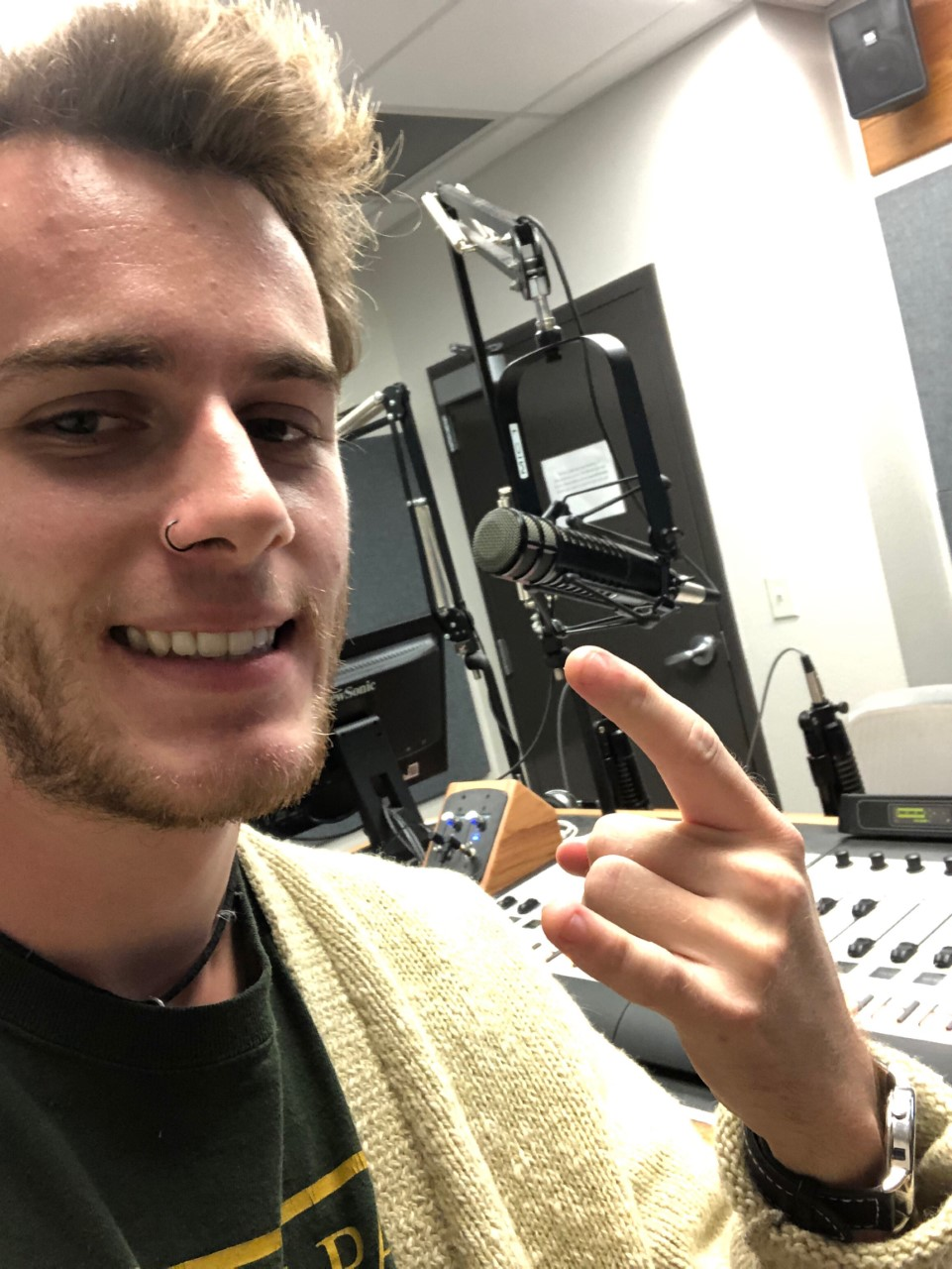 A photo of Dylan Holland's face with a radio studio as the background.