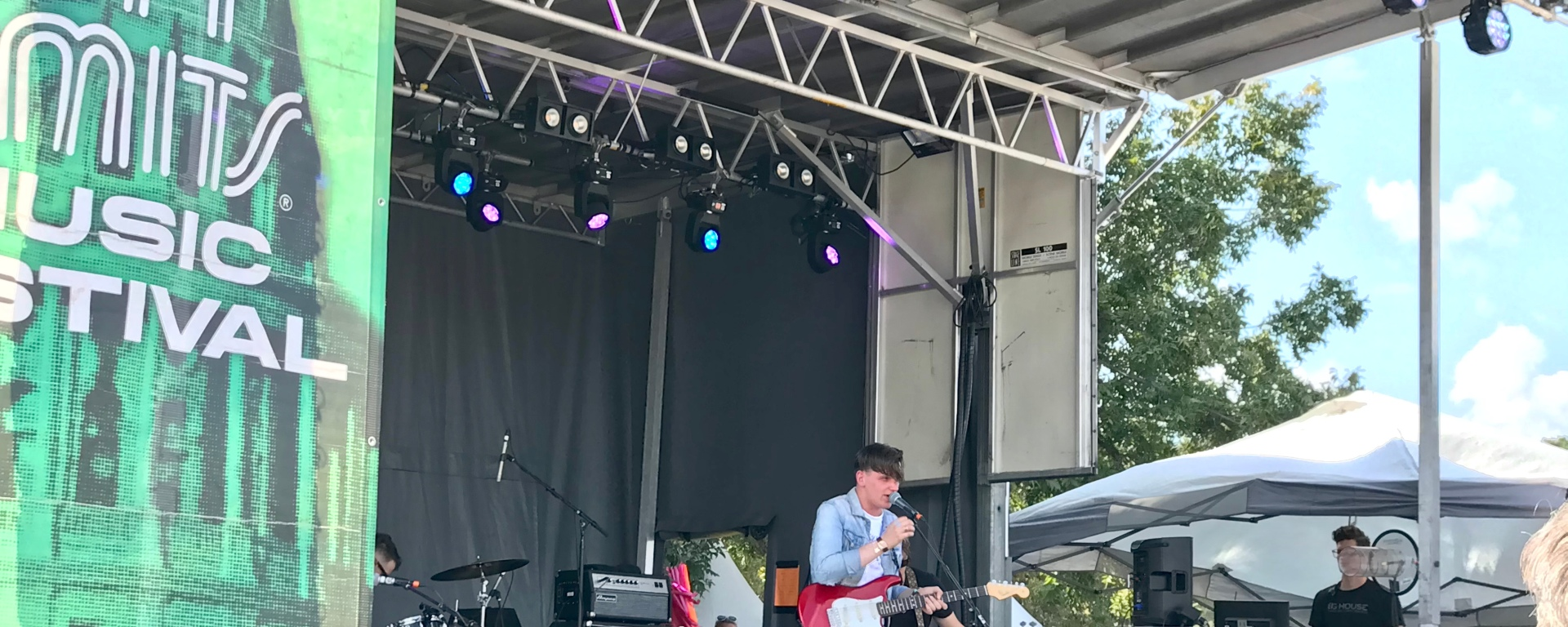 Singer / songwriter Patrick Droney plays live at Austin City Limits to a crowd of onlookers. The artist is wearing a blue jean jackets and holding a red guitar.