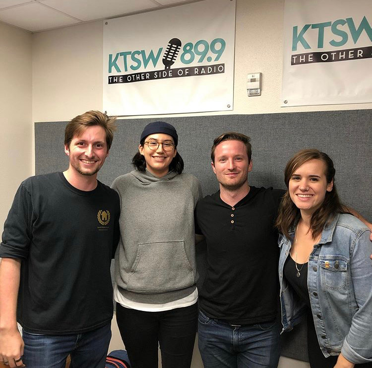 Two men and two women pose together in the KTSW booth