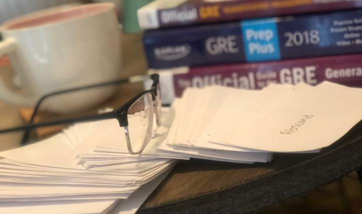 glasses sitting with a coffee cup and a stack of three GRE prep books Image title: GRE studying