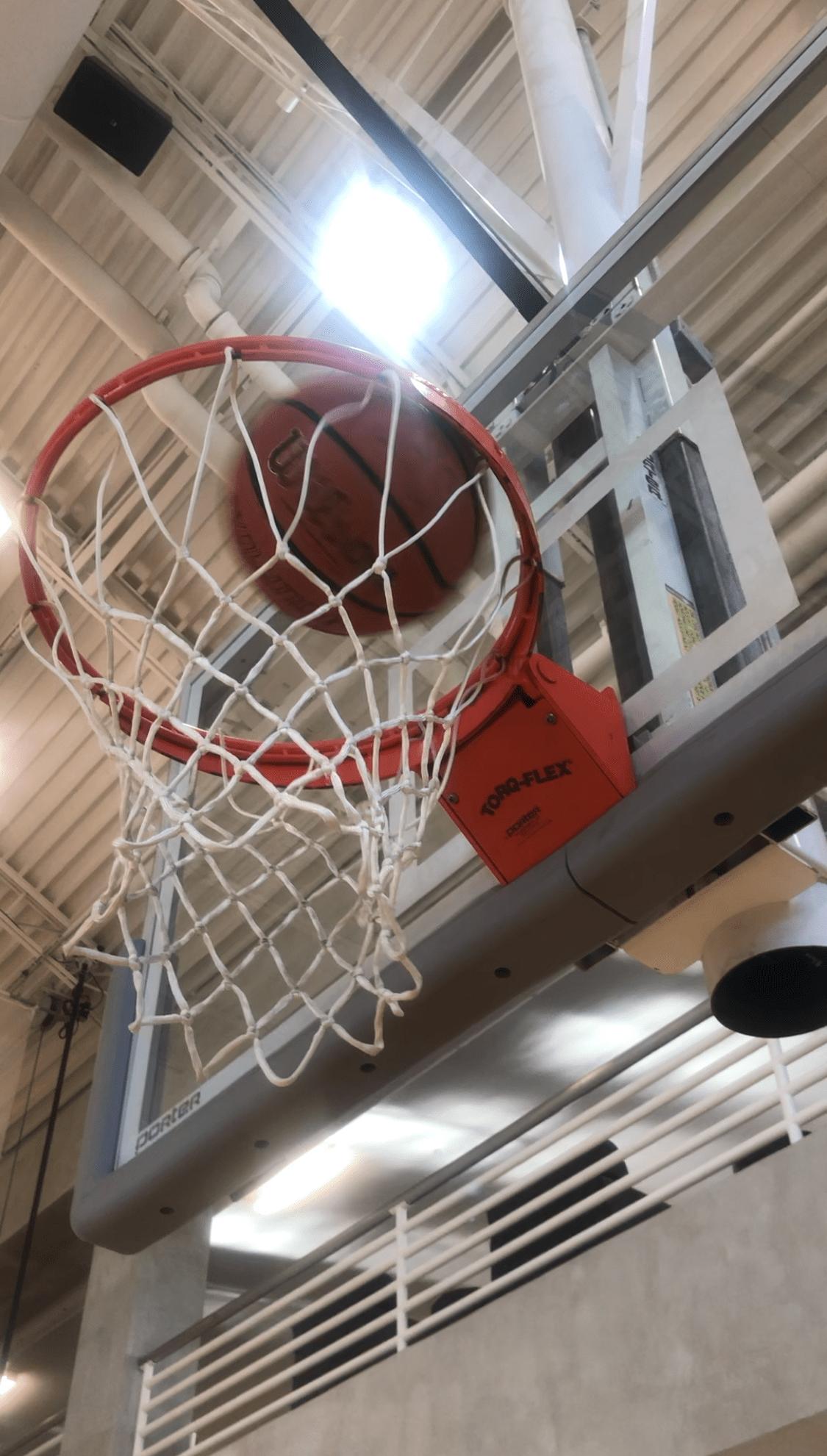 A basketball goes through a basketball hoop