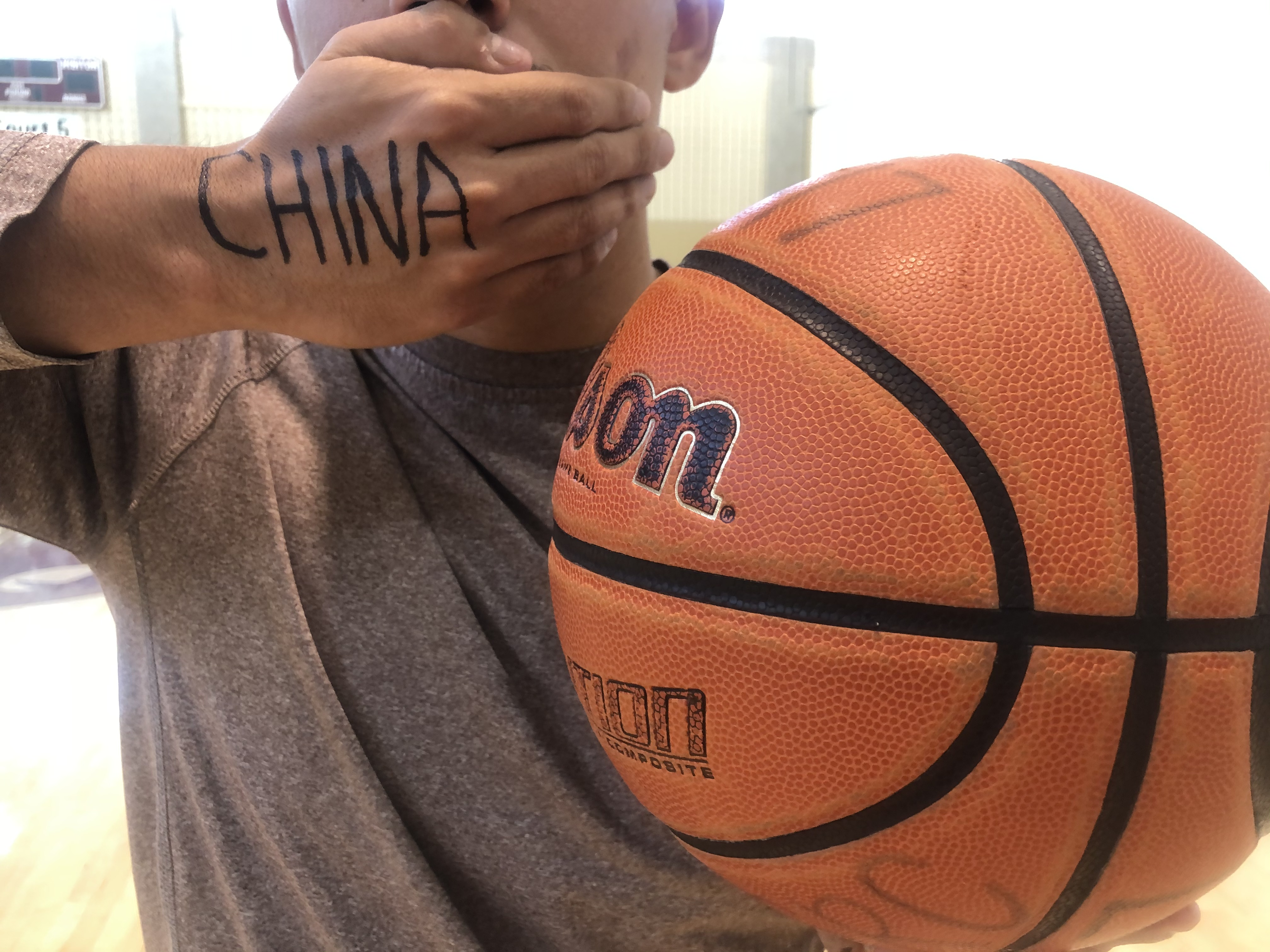 "A man stands with his hand over his mouth and ""China"" written on it, with a basketball in the other hand"