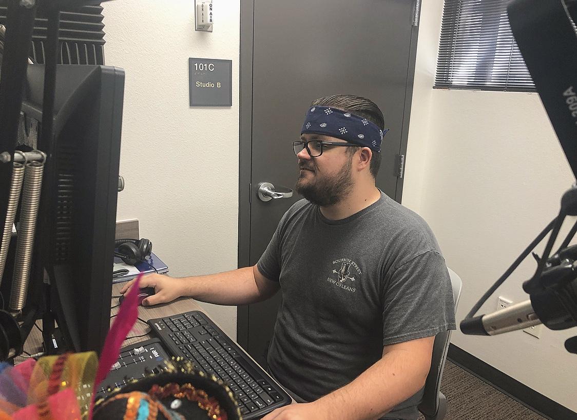 Man wearing a navy bandana and gray tshirt sits at desk looking at a computer.
