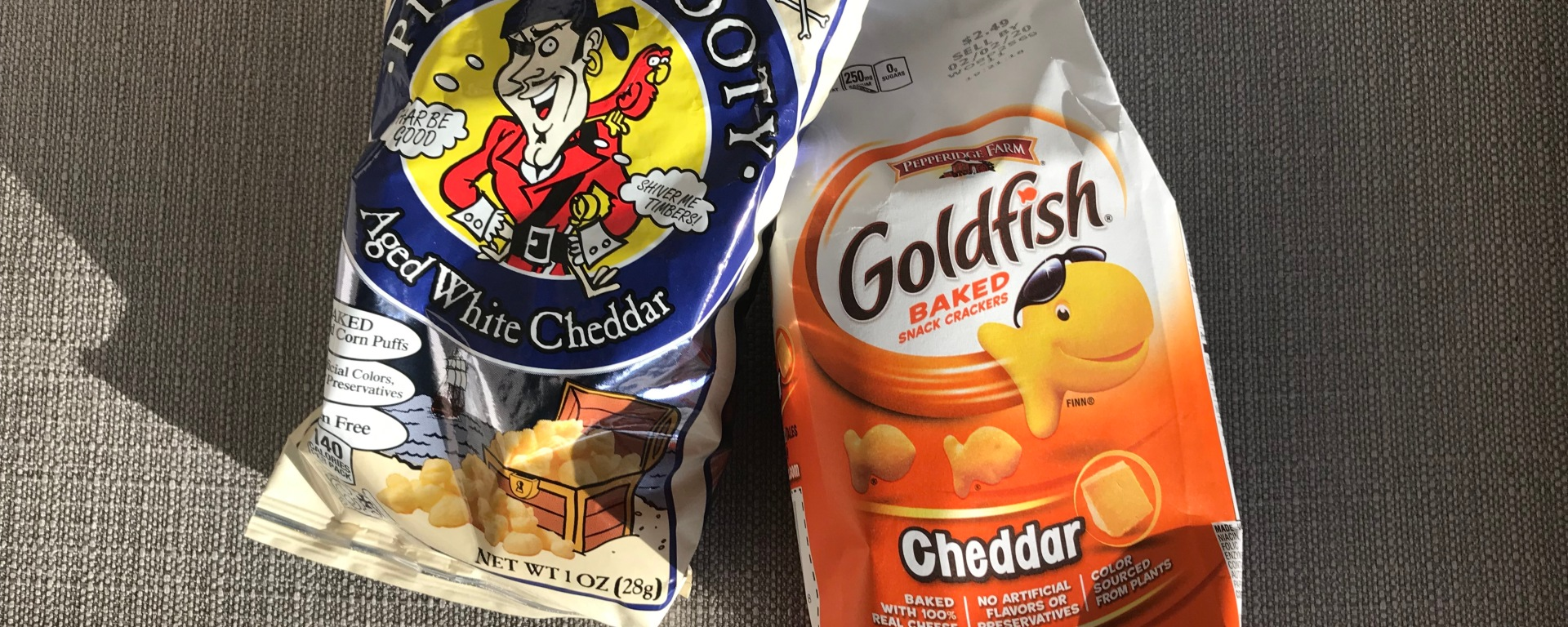 An image of a bag of Pirate's Booty and Goldfish on a couch
