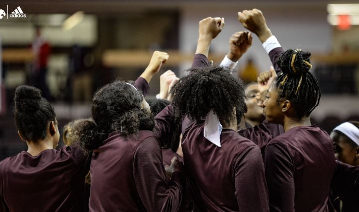 Women in Maroon Texas State shirts raise their hands together to break out of a huddle.