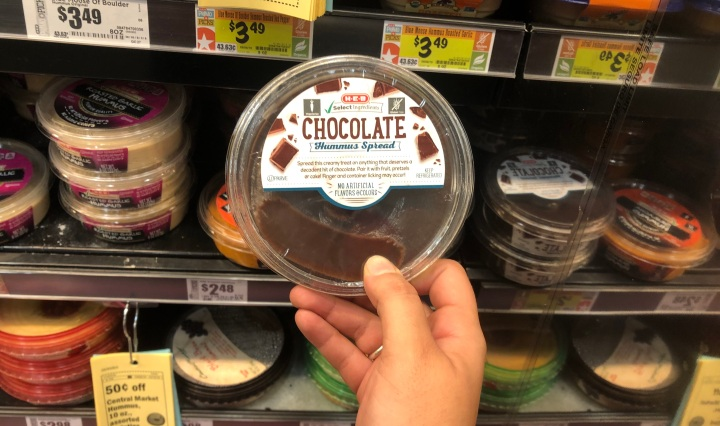 This is a picture of me holding a thing of unopened chocolate hummus at HEB in the Meal Simple section.