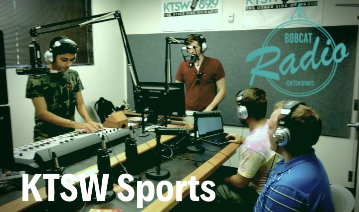 Four KTSW student workers in the studio with headphones on speaking into microphones.