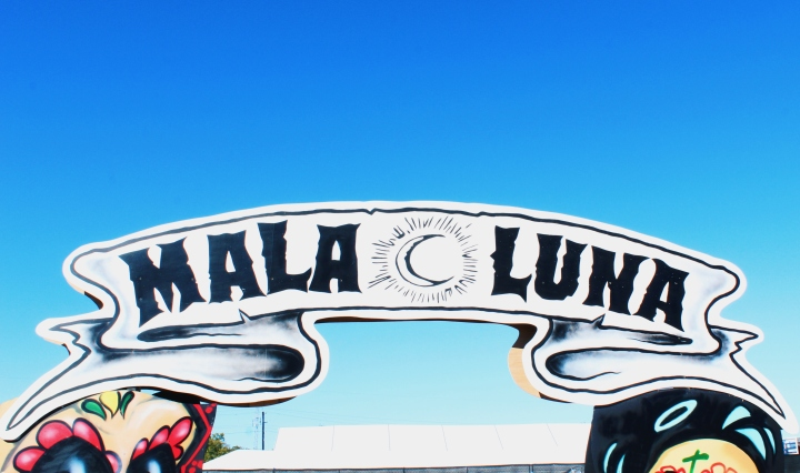 "A white sign made to look like a ribbon that says ""Mala Luna"" in black capital letters. Between the words ""mala"" and ""luna"" there is a crescent moon with lines around it, made to look like a sun. Below and on each side of the sign there are colorful skulls painted like sugar skulls from Day of the Dead celebrations. The background is a blue sky."