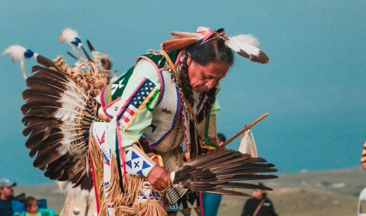 A Lakota Native American man wearing a colorful headdress and outfit