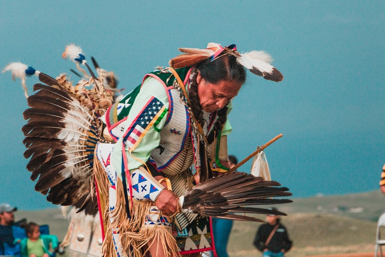 A Lakota Native American man wearing a colorful headdress and outfit