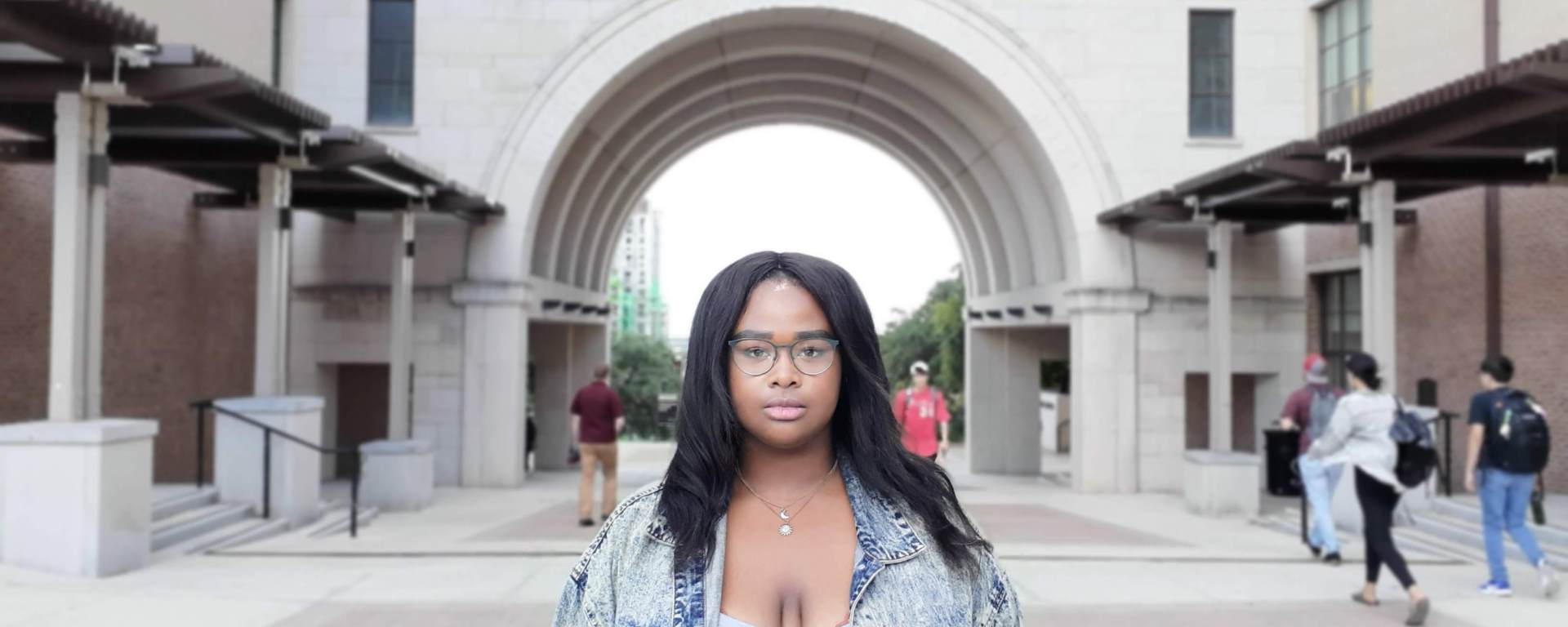 Timia Cobb stands in front of Texas State University UAC arch , wearing glasses, an ash wash grey jean jacket and grey shirt while students walk in the background.