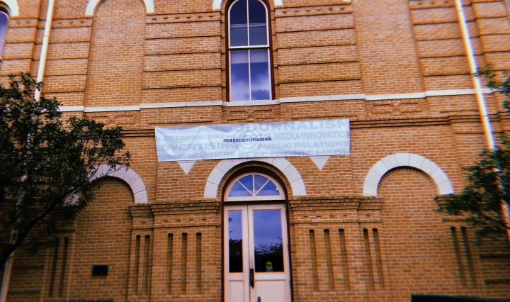 The outside of Old Main with a Mass Comm Week banner above the door