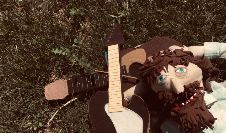 A puppet of a man with blue eyes and a brown beard and hair lies in the grass next to two guitars made of felt.