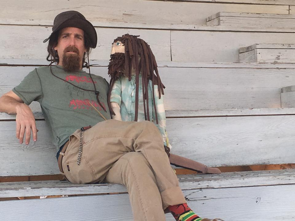 "A man wearing a hat, with a brown beard and dreadlocks, sits on a step wearing a shirt that says ""Smell Monsters Puppetry"" and holding a puppet version of himself."