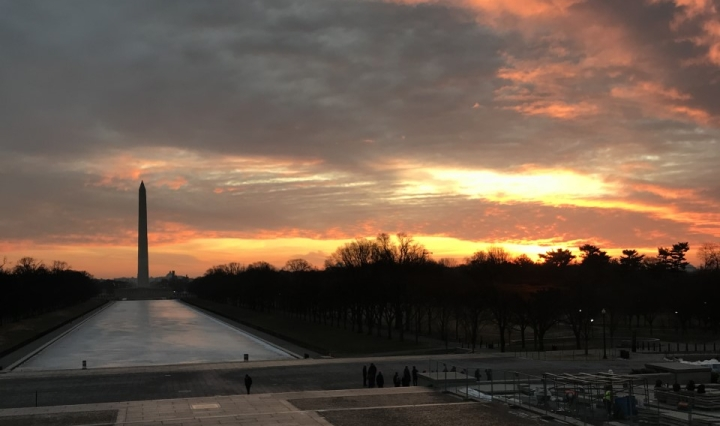 Clouds streaked with white and orange and sunlight are over a far-away photo of the Washington Monument.
