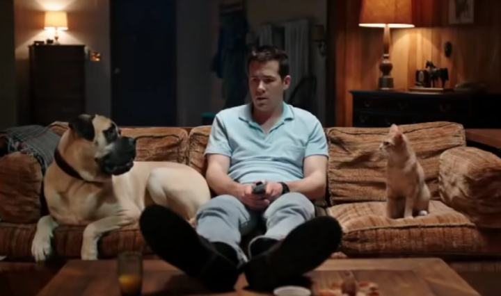 Jerry wears a blue polo shirt while sitting on his brown couch in between his dog and cat.