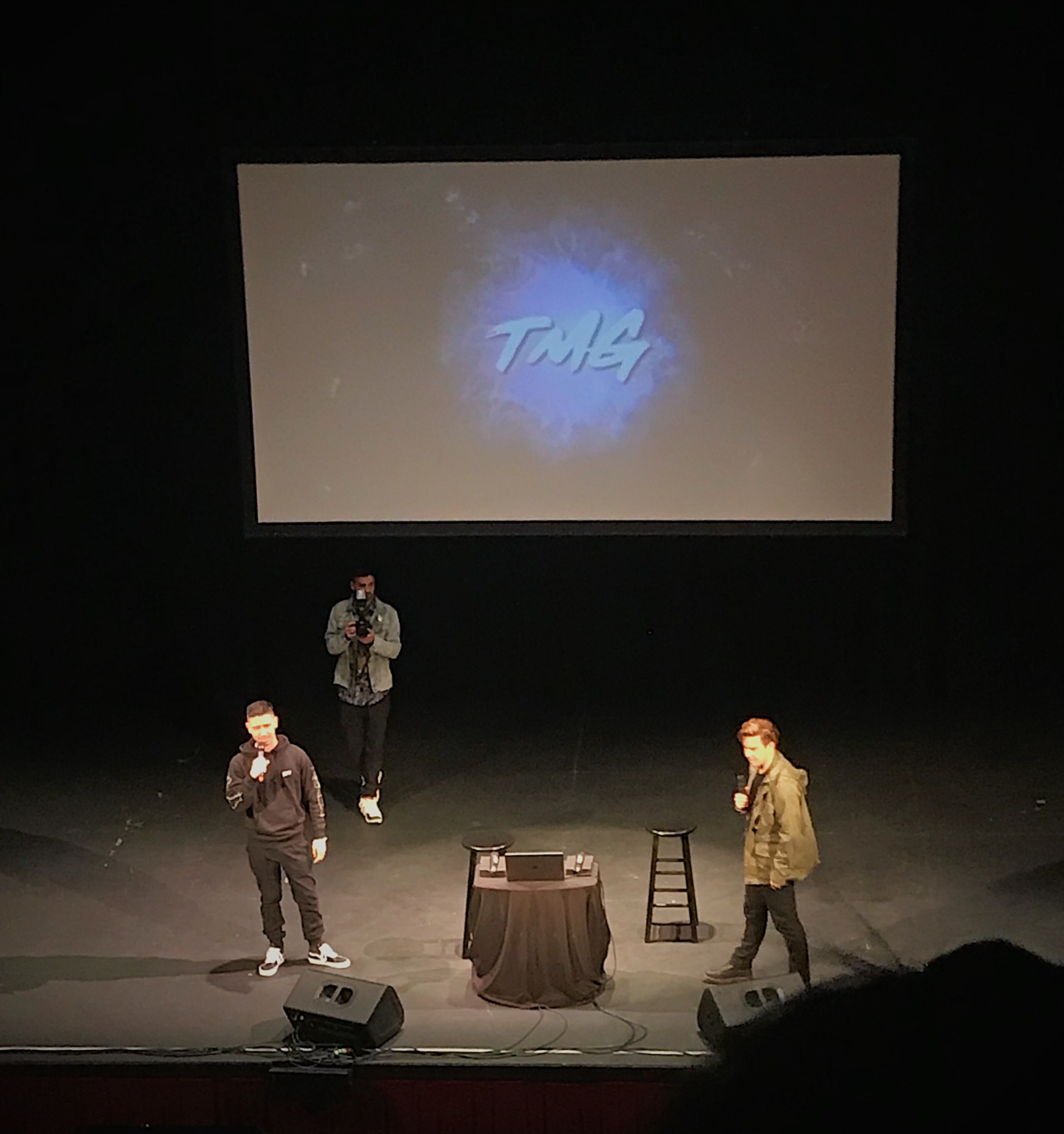 """Noel Miller stands left of Cody Ko on a theater stage. They are both spotlighted by overhead lights. A projector screen above them reads """"TMG"""" on top of a tye-dye blue background."""