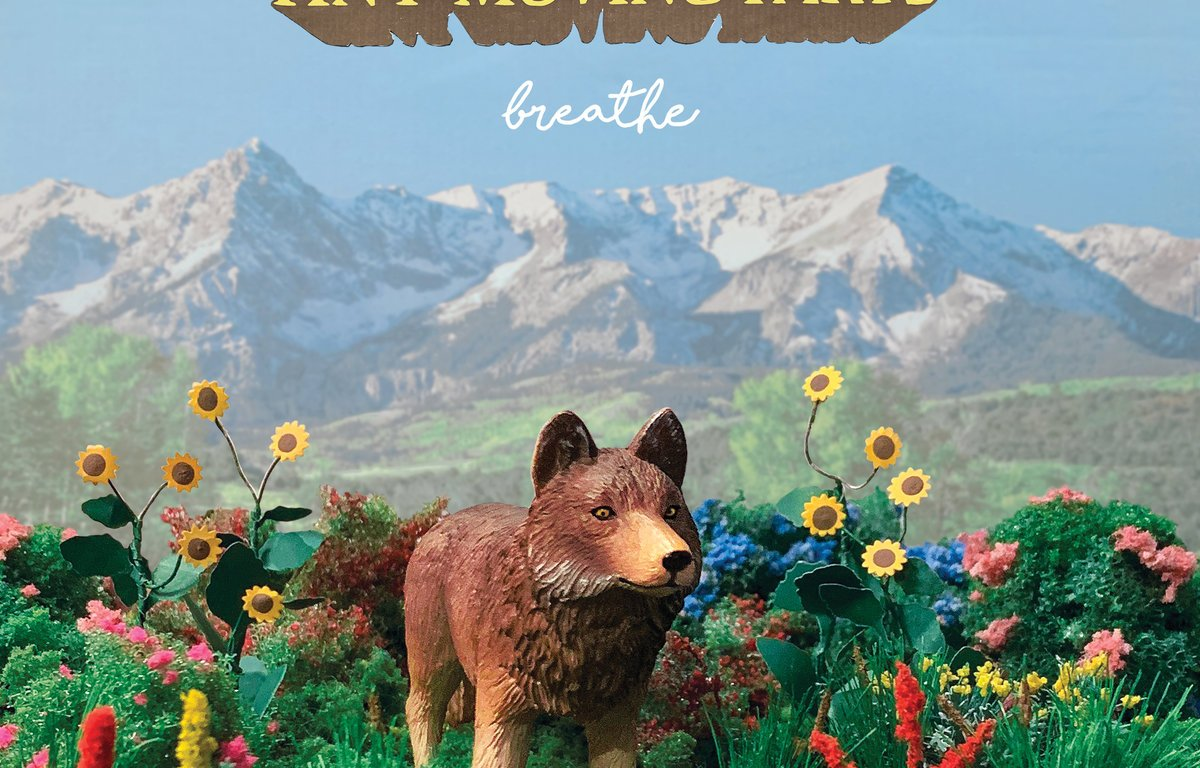 A toy wolf stands in a garden with a mountain in the background.