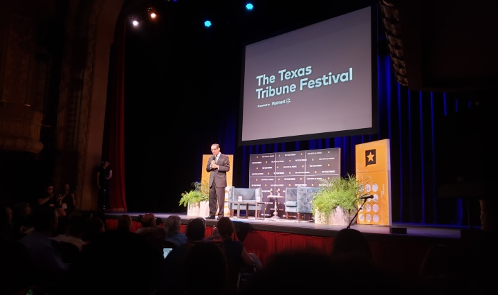 Evan Smith, the CEO of the Texas Tribune, stands on a stage decorated by Tribune backdrops, two chairs, and a coffee table.