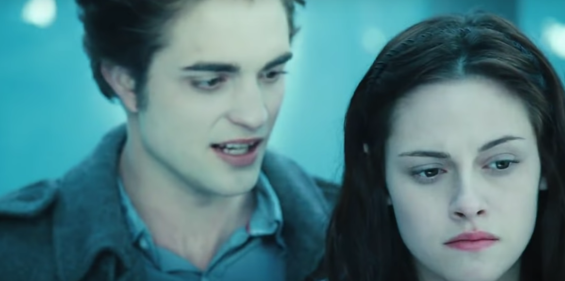 Two pale skinned teenagers stand, Edward the boy stands behind Bella