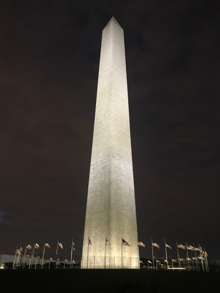 The Washington Monument up close, surrounded by multiple small American flags.