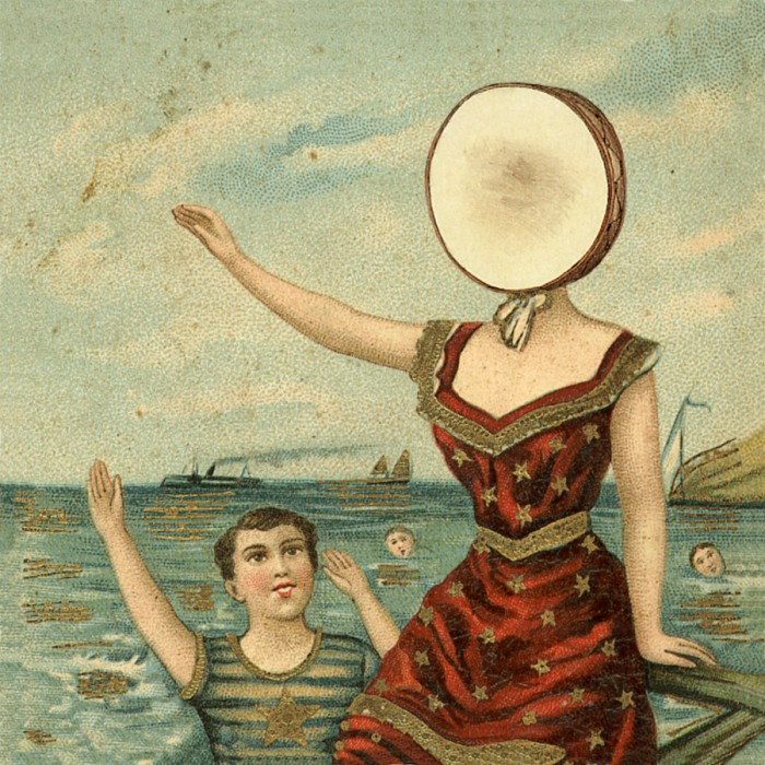 Two individuals sitting in water, one having what looks like a tambourine for a head.
