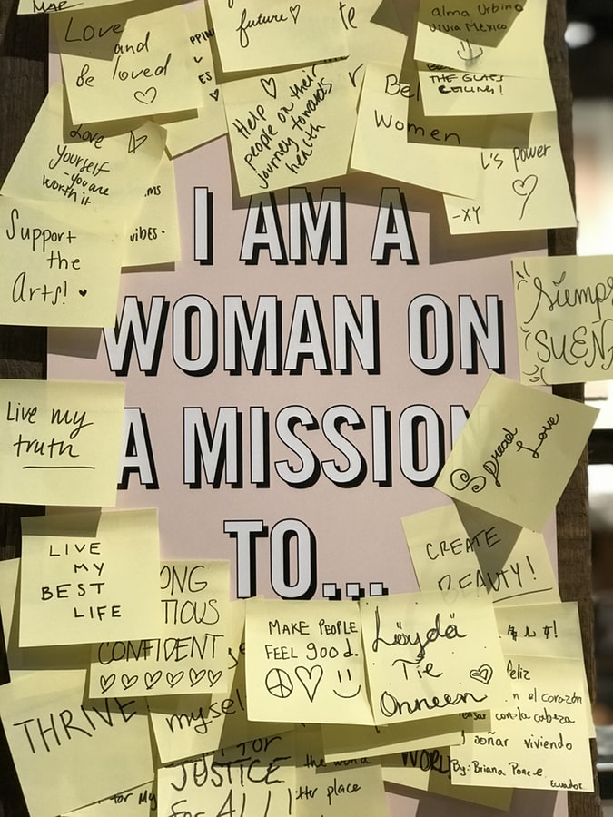 "A pink sign that says ""I am a woman on a mission to"" with yellow sticky notes all around."