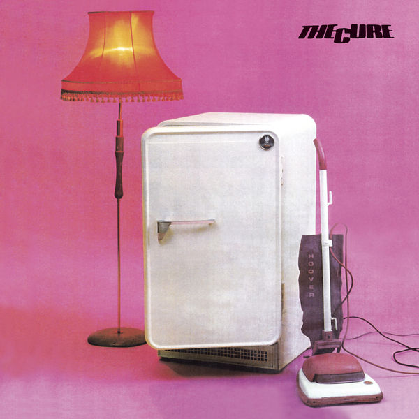 An album cover with a pink backdrop and a fridge, lamp and vacuum