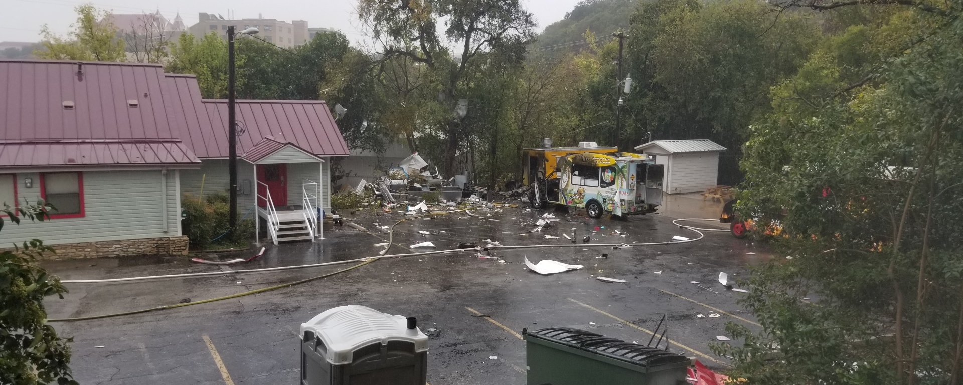A parking lot with metal and trash scattered everywhere.