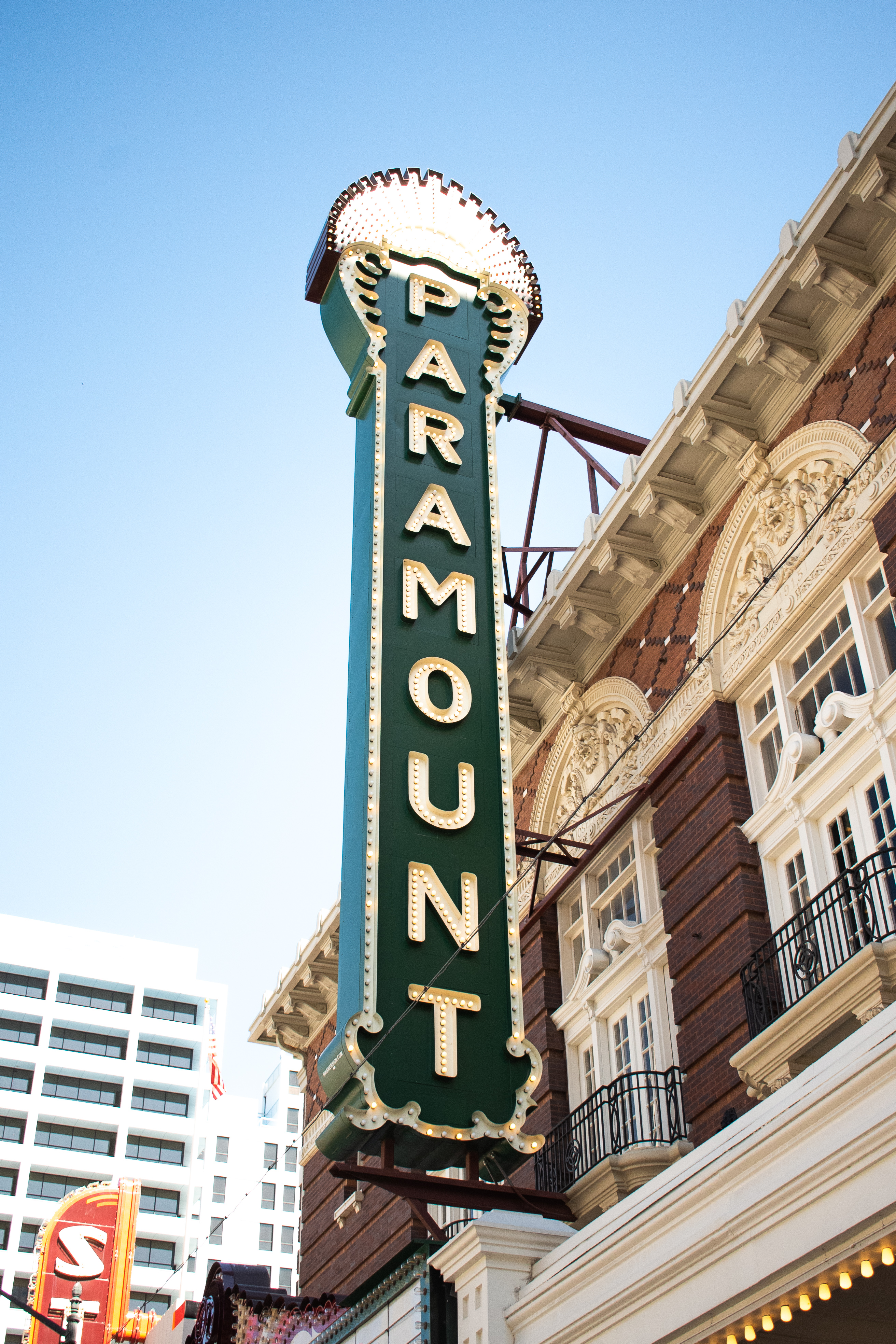 Green sign that is vertical has the word Paramount spelled out on it. The sign is attached to a older building.