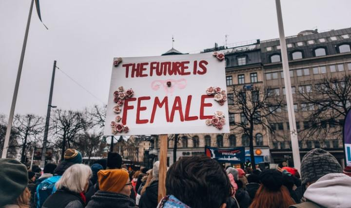 "A sign with ""the future is female"" written on it with roses attached."