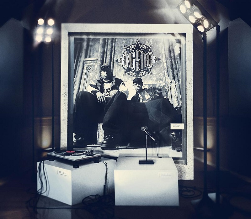 "Album art for Gangstarr ""One of the Best Yet"", the cover shows a black and white framed picture of DJ Premier and Guru. A microphone and turn-table rest on white boxes in front of the image."
