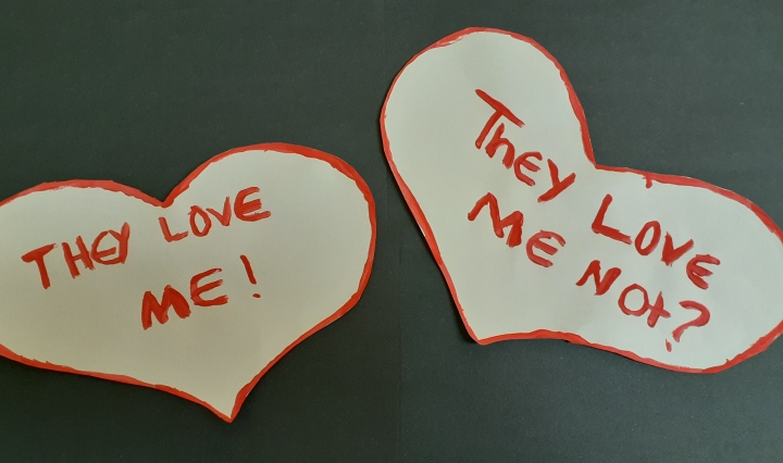 "Two white hearts outlined in red paint, one saying, ""They love me!"" The other saying ""They love me not?"" On a black background."